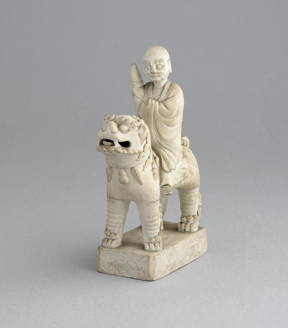 Biscuit beeldje van een Wijze gezeten op een boeddhistische leeuw