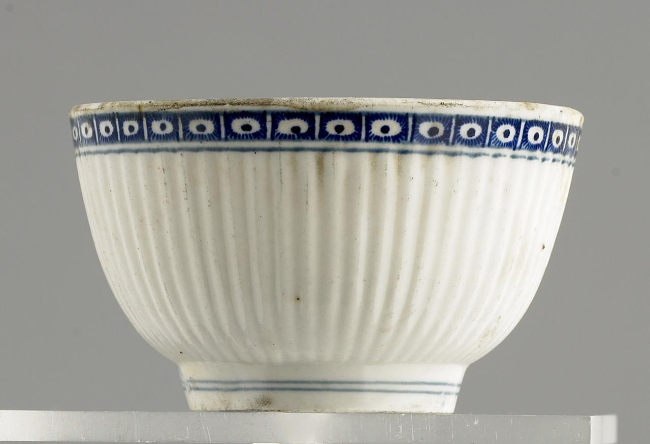 Een kopje en twee schoteltjes blauw en wit aardewerk
